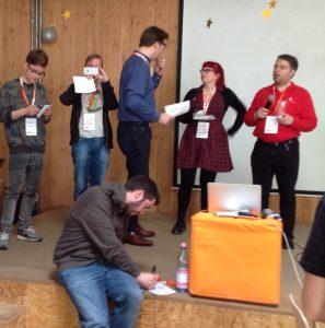 Teilnehmer des Barcamps Berlin stehen auf der Bühne und stellen ihre Session vor.