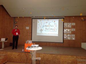 Jan Theofel moderiert das Barcamp Berlin. Er hat ein Mikrofon in der Hand und steht auf der Bühne.