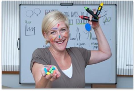 Visual Facilitator Manuela Kordel steht vor dem Flipchart, lächelt und hat bunte Kreide und Marker in der Hand.